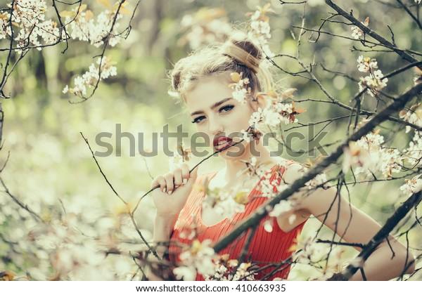 Beautiful sensual young woman enjoying beauty in a flowering spring garden