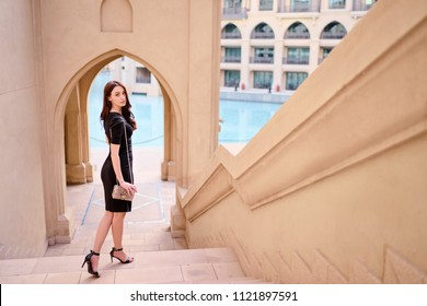 Beautiful sensual young woman with long dark hair in black dress walking on Dubai Downtown street.