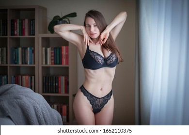Beautiful sensuality brunette woman, has sexy body, big breast, dressed in black erotic underwear, panties and bra. Home portrait.  Nature romantic pure makeup. Fashion style portrait.