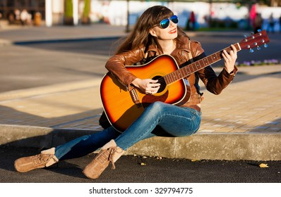 Beautiful sensuality elegance haired woman, has happy fun cheerful smiling face, brown leather jacket, blue jeans and sunglasses, sexy lips. Playing in instrument guitar. Music in urban city.