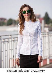 Beautiful sensuality elegance lady haired hair woman, has happy fun face, white business blouse, slim body, blue sunglasses. Urban city portrait. Nature lifestyle. Sunny day.