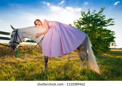 Beautiful sensuality elegance lady woman, sitting  and riding a horse. Clothed long luxury pink dress. Amazing portrait in nature. People and animals. Fairy summer landscape.