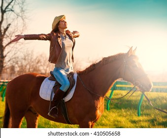 Beautiful sensuality elegance woman cowgirl, riding a horse. Clothed blue jeans, brown leather jacket and hat. Has slim sport body. Portrait nature. People and animals. Equestrian. Amazing sunset