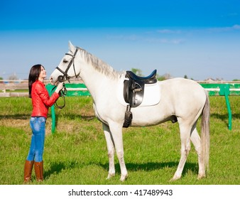 Beautiful sensuality elegance woman cowgirl near white horse. Clothed blue jeans, red leather jacket. Has slim sport body. Portrait nature. People and animals. Equestrian. Amazing day.