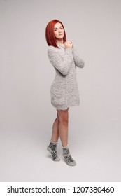 Beautiful and sensuality red haired girl wearing long gray knit sweater and warm socks posing at studio, looking at camera. Comfort and cozy in cold winter evening. Home woman look.