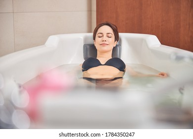 Beautiful serene relaxed young Caucasian lady with her eyes closed lying in the hydromassage bathtub