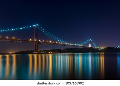 Beautiful and serene view of the Tagus River and the 25 of April Bridge (Ponte 25 de Abril) at night, in Lisbon, Portugal; Concept for visit Lisbon