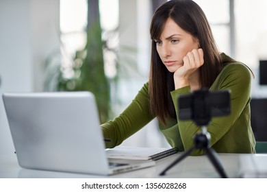 Beautiful serious Caucasian businesswoman sitting in modern office and using laptop.