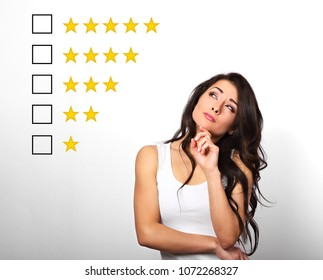 Beautiful serious doubt woman with finger under the face thinking and looking up to vote to five yellow star to increase ranking on white background. The online rating, evaluation, rewiew.