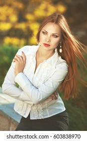 Beautiful serious elegant woman in white shirt with pearl earrings and long hair in the park at sunny day