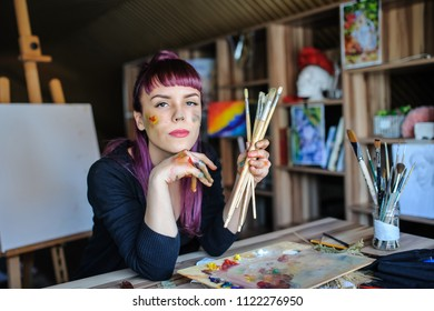 Beautiful and serious female artist with purple hair and dirty hands with different paints on them, holding paintbrushes in her art studio.