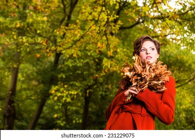 Beautiful serious romantic girl with short hair holding a bunch of rusty leaves in autumn day