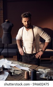 Beautiful serious tailor with beard in white shirt with brown leather suspenders standing near wooden table with threads, apron and scissors and thinking in amazing atelier with antique furniture