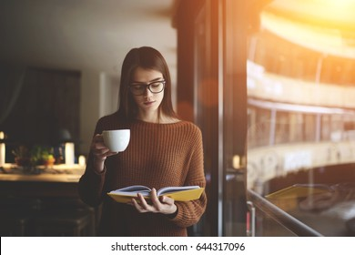 Beautiful serious teen girl in eyeglasses attentively reading exciting poetry standing in comfortable campus,charming woman spending free time in cozy cafeteria and preparing homework using manual