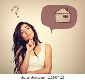Beautiful serious thinking woman looking up on small illustration house in bubble above and asking the questions. Insurance protection concept, investment to safety money. Vintage color style