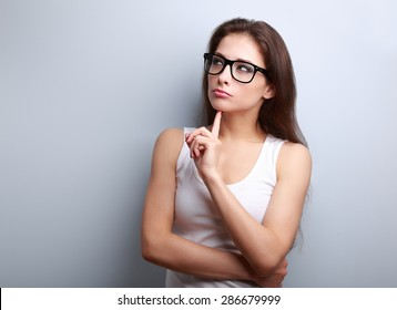 Beautiful serious thinking young woman looking up on empty copy space