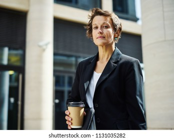 Beautiful serious woman in suit holding paper cup of coffee and looking at camera standing on street in sunlight