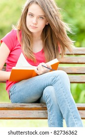 beautiful and serious young student girl sitting on bench, holding book in her hands and looking into the camera. Summer or spring green park in background
