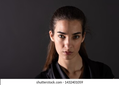 A beautiful serious young woman in an elegant black dress standing in front of a grey background in a studio.