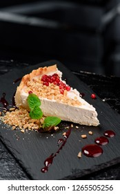 Beautiful serve of cheesecake, decorated with cranberries, mint, pine nuts and red syrup, on a black plate on a dark background. close up