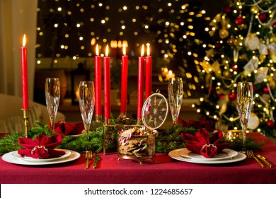 Beautiful served table with candles, Red tablecloth and napkins, white china, gold cutlery, crystal champagne glasses. Living room decorated with lights and Christmas tree. Holiday setting