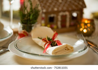 Beautiful served table with decorations, candles and lanterns. Little gingerbread house with glaze on white tablecloth. Living room decorated with lights and Christmas tree. Holiday setting close up.