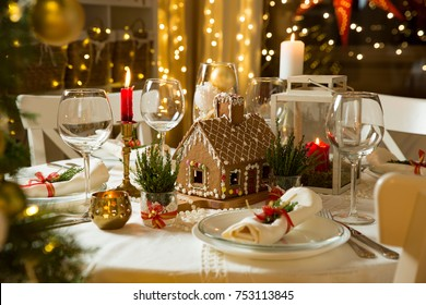 Beautiful served table with decorations, candles and lanterns. Little gingerbread house with glaze on white tablecloth. Living room decorated with lights and Christmas tree. Holiday setting