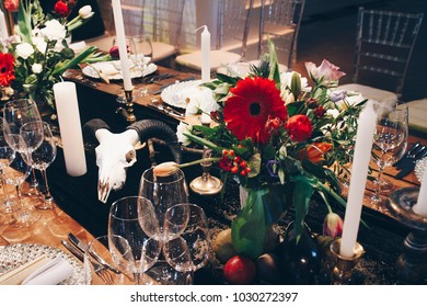 Beautiful served wedding table with decor as candles, flower arrangements . Banquet dinner party in style Freemasonry (Masons) with skulls and horns