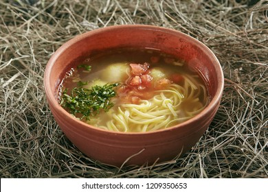 Beautiful Serving Vintage Ceramic Bowl of Homemade Noodle Soup Arishta with Chicken Meatballs. Clear Sturdy Seasoned Broth with Turkey Meat Balls, Egg Spaghetti and Greens on Rustic Background