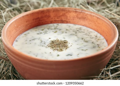 Beautiful Serving Vintage Ceramic Bowl of Homemade Kefir Soup Dovga or Tarator. National Sour-Milk Meal of Azerbaijani Cuisine with Yogurt, Herbs and Greens on Rustic Background Close Up