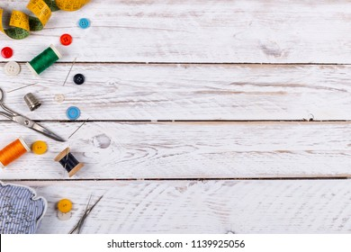 Beautiful set of scattered across white wooden table metal scissors, assorted buttons and sewing spools with colorful threads and tape measure from above