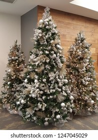 Beautiful set of three christmas trees decorated with silver balls, gold garland, shiny balls and glowing lights.
