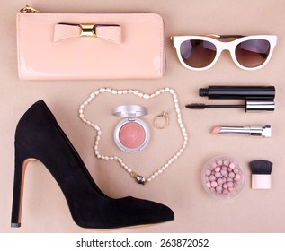 beautiful set of women's fashion accessories and cosmetics on a beige background
