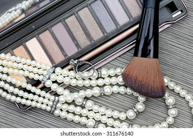 Beautiful set of women's fashion accessories and cosmetics, Professional make-up, luxury earings, Makeup brush and eyeshadow.