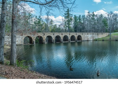A beautiful seven arch bridge crosses over Byrd lake in the state park with two geese swimming in the calm water on a sunny day in springtime