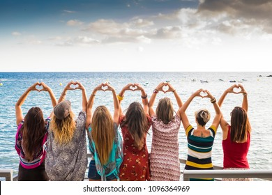 beautiful seven girls from the backside doing a heart with the hands looking at the ocean waiting the sunset in vacation leisure activity. friendship all together forever concept travel to sea party