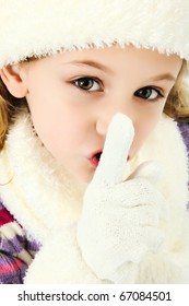 Beautiful seven year old girl dressed for winter with hat and gloves and scarf making quiet or secret gesture with hands.
