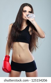 Beautiful sexual boxing girl, drinking water, fitness, on a grey background