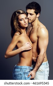 Beautiful sexual couple topless playing in love games. Jeans style. Studio shot.