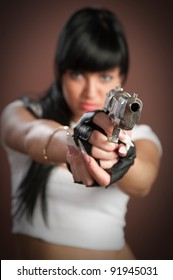 Beautiful sexual girl brunette with gun on brown background