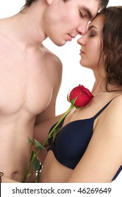 Beautiful sexual half naked couple with red rose isolated over white background