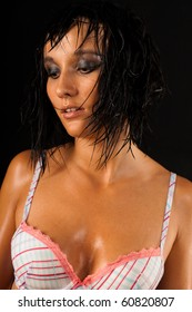 Beautiful sexual wet girl in white swimsuit with expressive eyes in the drops of water on the black background