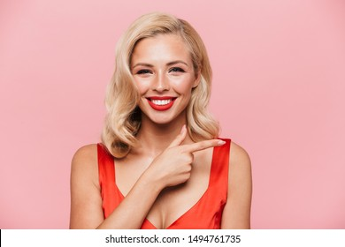 Beautiful sexual young blonde woman wearing red cocktail dress standing isolated over pink background, pointing finger away