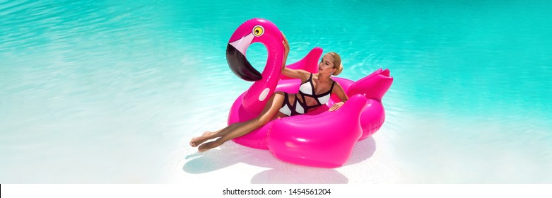 Beautiful sexy, amazing young woman in a swimming pool sitting on an inflatable pink flaming and laughing, tanned body, long hair, black and white bikini, fashionable accessories - Image