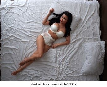 beautiful sexy Asian girl in lingerie lying on bed, top view