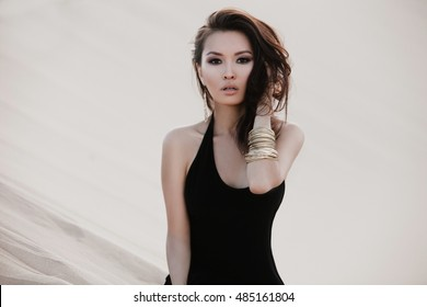 Beautiful sexy asian woman model posing in desert