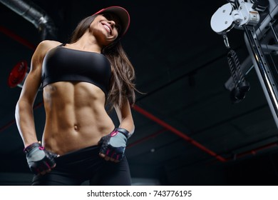 Beautiful sexy athletic young brunette Caucasian girl working out training pumping up abdominal muscles abs sixpacks in the gym on machines gaining weight and poses fitness and bodybuilding concept