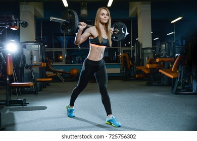 Beautiful sexy athletic young Caucasian girl working out in the gym training legs quadriceps and hamstrings on machines and with a barbell pumping up gaining weight fitness and bodybuilding concept
