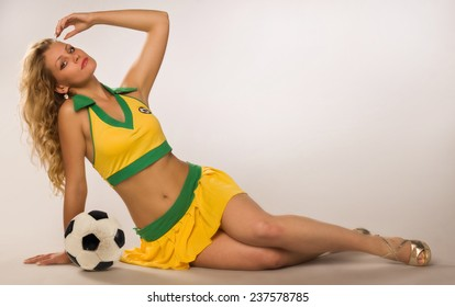 beautiful sexy blond cheerleader whit soccer ball on a gray studio background