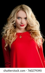 beautiful sexy blond girl in a bright red dress posing in the studio on a black background